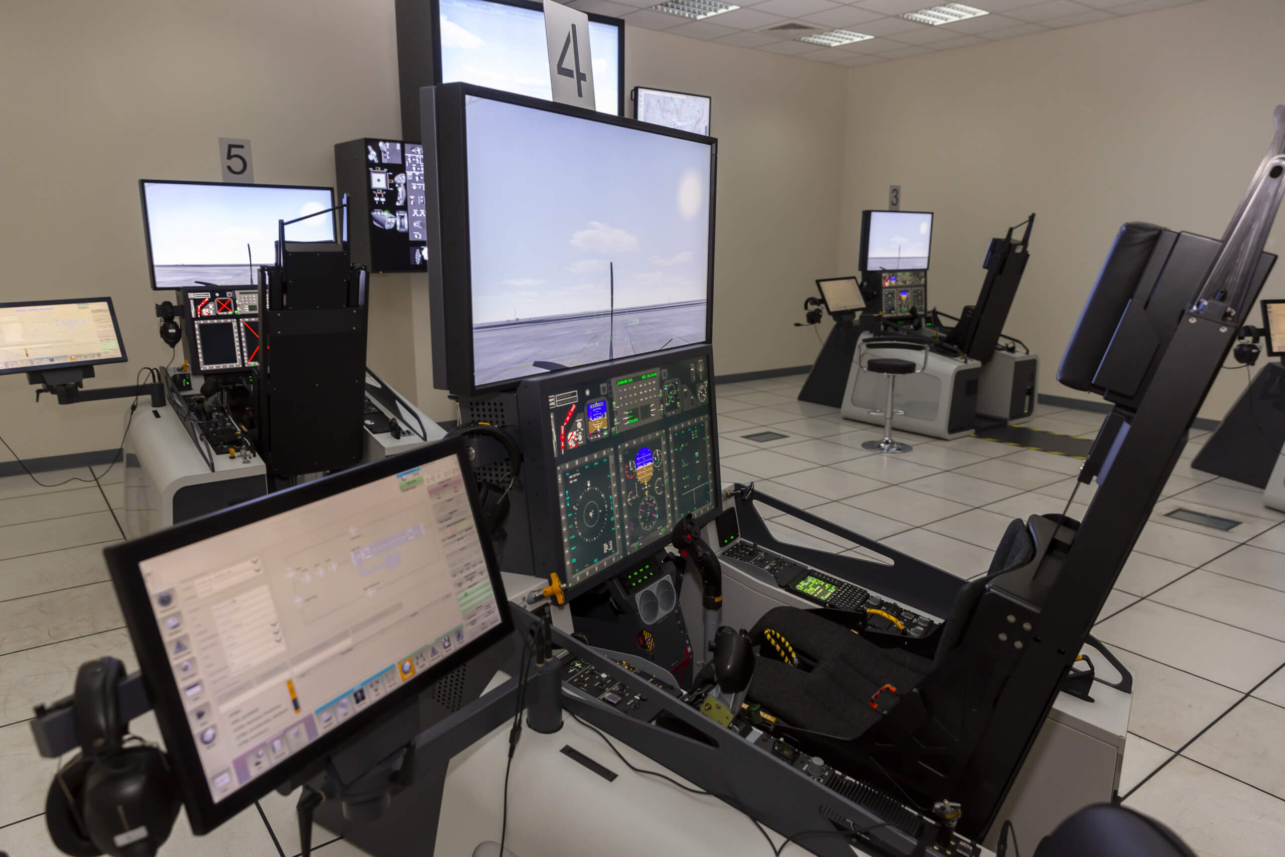 Image of fighter aircraft simulator training room with multiple screens and controls to practice test environment simulation