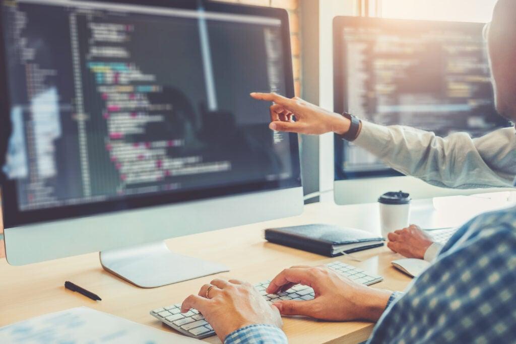 Imagen que muestra dos codificadores mirando el monitor con código en la pantalla. Uno de los codificadores apunta al monitor, el otro tiene las manos en el teclado.