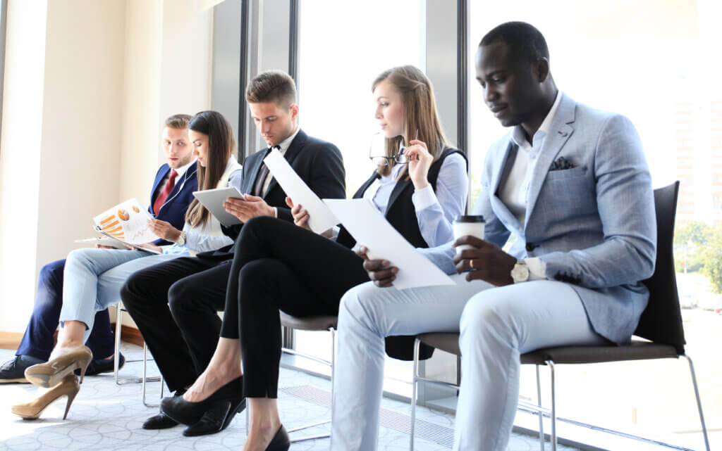 Candidates reviewing QA interview questions before a job interview.